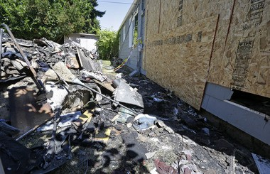 Debris from a fire fills the backyard next to the now boarded-up house where the night before a man used a can of spray paint and a lighter as a makeshift blowtorch to kill a spider, Wednesday, July 16, 2014, in Seattle.