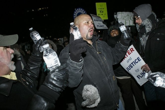 Dan Reyes, president of the UAW Local 599 in Flint, hands out bottles of Flint water to protestors during a rally outside of the Michigan State Capitol Building during Gov. Rick Snyder's State of the State address on Tuesday, Jan. 19 2016 in Lansing.