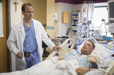 In this June 18, 2016 photo provided by the Mayo Clinic, Dr. Samir Mardini checks on his patient, Andy Sandness, days after leading a team that performed the first face transplant surgery at the medical center. (Eric M. Sheahan/Mayo Clinic via AP)