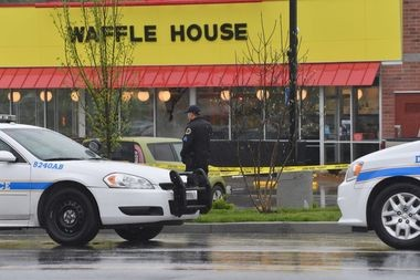 Law enforcement officers stand outside a Waffle House in Nashville, Tenn., where four people were killed and two were wounded after a gunman opened fire on April 22.
