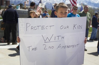 "Joseph Jensen, 10, of Spanish Fork, Utah, carries a ""Protect our kids with the 2nd Amendment"" sign while attending a pro-gun rally on the steps of the State Capitol in Salt Lake City last month. (AP Photo)"