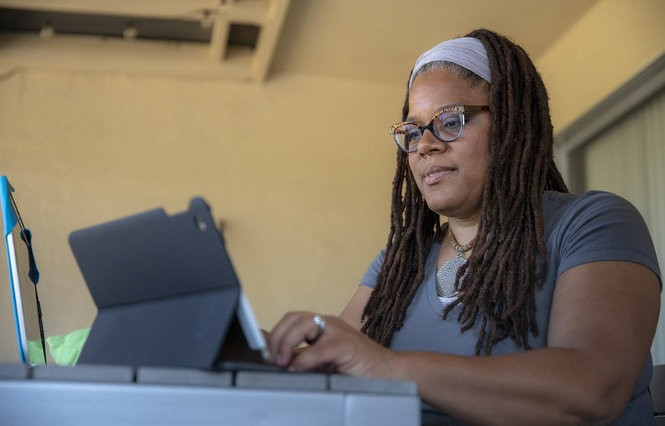 "Brittany Walker Pettigrew, a child welfare worker, who helps moderate the ""Guns: An American Conversation"" Facebook group, works at her home in Oakland, Calif., June 8, 2018. (Robert Durell)"