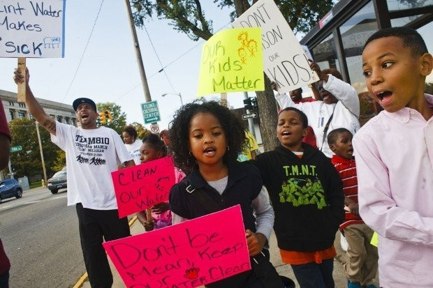 Protestors march along Saginaw Street demanding clean water outside of Flint City Hall in Flint, Mich. on Wednesday Oct. 7, 2015.