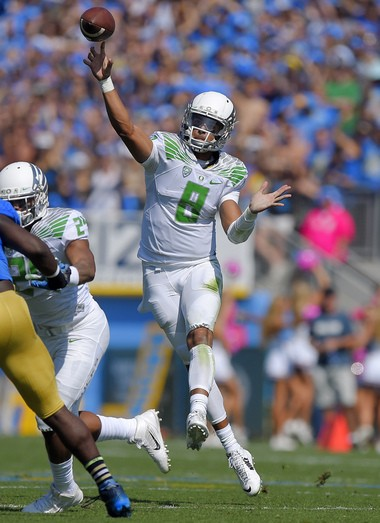 In this Oct. 11, 2014, file photo, Oregon quarterback Marcus Mariota passes during the first half of an NCAA college football game against UCLA in Pasadena, Calif. Mariota goes into Saturday's Dec. 13, 2014, Heisman Trophy ceremony as the clear front runner. (AP Photo/Mark J. Terrill, File)