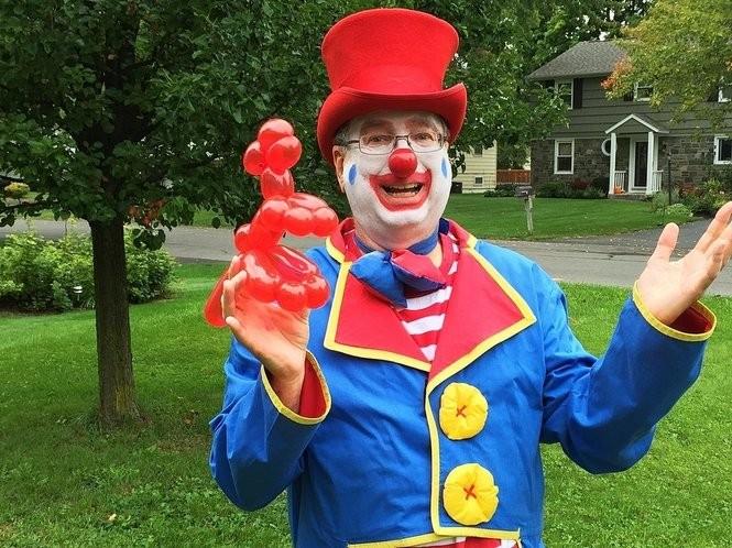 "Ron Cain, dressed as ""Yo-Yo the Clown"", holds a balloon dinosaur he made."