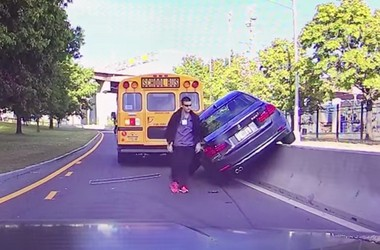 A BMW driver can be seen exiting his vehicle after crashing into a concrete barrier while trying to pass a school bus in Albany on Tuesday, Oct. 11, 2016.