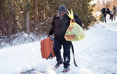 A Somali man carries his belongings after crossing into Canada over the U.S.-Canada border near Hemmingford, Quebec, on Friday, Feb. 17, 2017. A number of refugee claimants are braving the elements to illicitly enter Canada. (Paul Chiasson/The Canadian Press via AP)