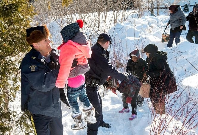 Family members from Somalia are helped into Canada by Royal Canadian Mounted Police officers along the U.S.-Canada border near Hemmingford, Quebec, on Friday, Feb. 17, 2017. A number of refugee claimants are braving the elements to illegally enter Canada. (Paul Chiasson/The Canadian Press via AP)