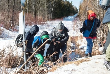 A family of asylum claimants crosses the border into Canada from the United States, Monday, Feb. 20, 2017, near Hemmingford, Quebec. A growing number of people have been walking across the border into Canada to claim refugee status. (Paul Chiasson/The Canadian Press via AP)