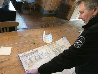 Ed Brennan, general manager of Beak and Skiff Apple Orchards and 1911 Established spirits, looks over plans for the company's new rickhouse on Route 20, which will hold barrels for aging whiskey.