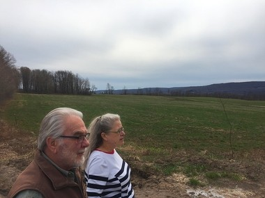 Greg Scammell and his wife, Kimberly Scott, look out over the field at the end of Markland Road, in the town of Lafayette, where a 2.4-million gallon manure pit is planned. Scammell and Scott say they're concerned about odors and contamination of wells.