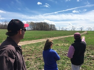 Mike Greip, partner in Preble Hill Dairy Farm (left), and Elizabeth Meyer, spokeswoman for the American Dairy Association, look on as Mark Burger, executive director of the Onondaga County Soil and Water Conservation District, points to a field at the top of Markland Road in LaFayette, where the farm plans to build a manure storage pit.
