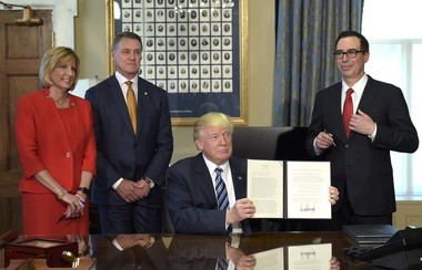President Donald Trump shows a memorandum he signed on Orderly Liquidation Authority at the Treasury Department in Washington, Friday, April 21, 2017. From left are, Rep. Claudia Tenney, R-N.Y., Sen. David Perdue, R-Ga., and Treasury Secretary Steven Mnuchin. (AP Photo/Susan Walsh)