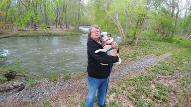 Luanne Caswell holding her dog, Roxie, by Nine Mile Creek, where she fell in.