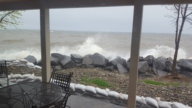 """The view of Lake Ontario from a house in Scriba in Oswego County. """"We are flooding from both sides, the lake and the wetlands on the opposite side of the road, giving us nowhere to pump or basement water. Erosion is incredible. It is incredibly frightening with today expected to be 5-7 foot waves,"""" wrote one reader."""