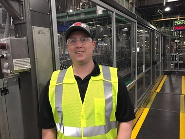 "Bryan Sullivan, general manager of the Anheuser-Busch brewery near Baldwinsville, NY, in front of the brewery's new ""multi-packing"" machine. It can package multiple-size packages at one time."