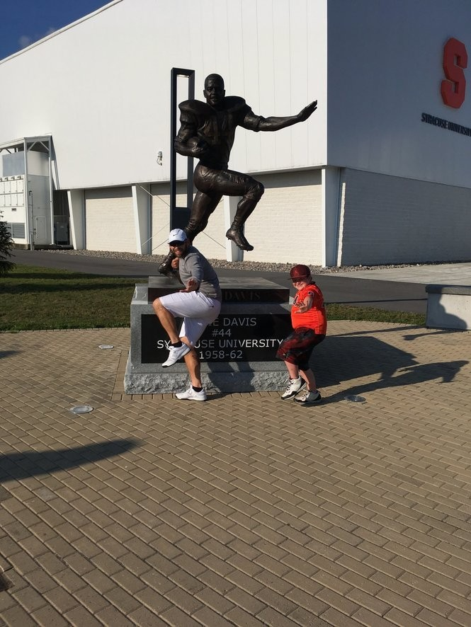 CJand Justin do the Heisman pose in front of the Ernie Davis statue at Plaza 44.