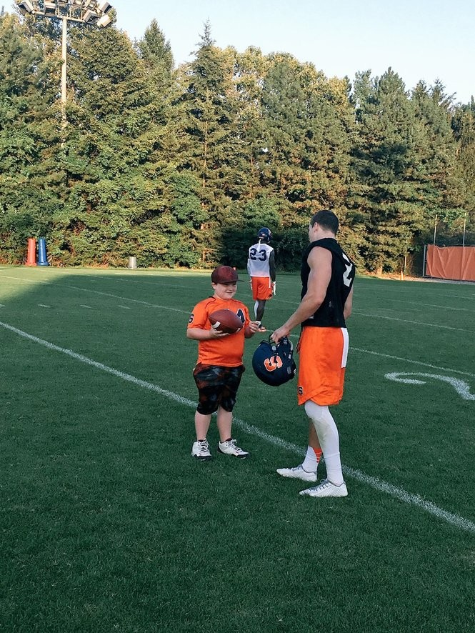 CJ exchanges throwing tips with Syracuse quarterback Eric Dungey.