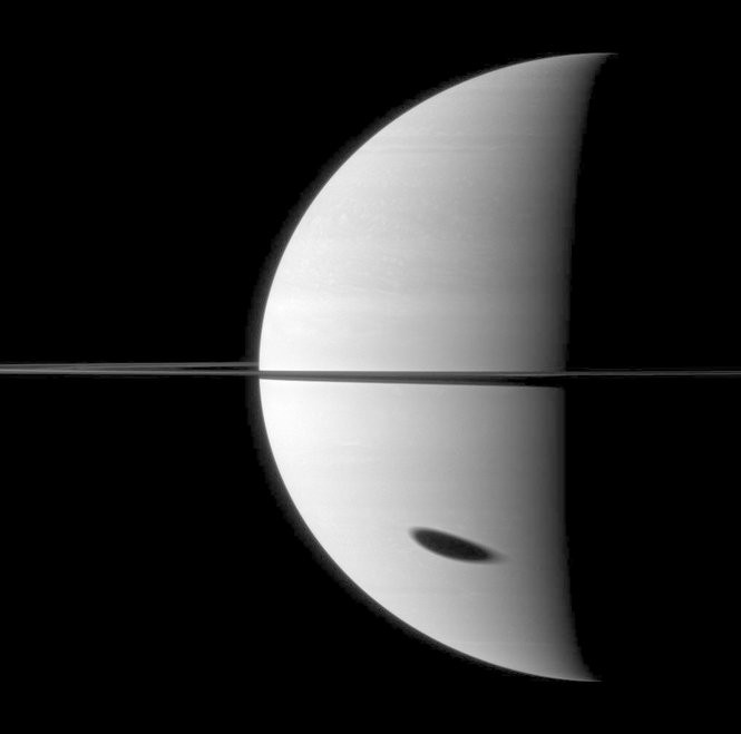 Titan casting a shadow on Saturn's surface, as captured by the Cassini satellite.