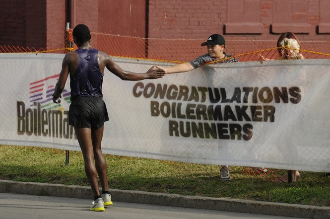 A young boy congratulates an early finisher during the Boilermaker 15K Run in Utica in 2010. More than 10,000 runners competed in the run.