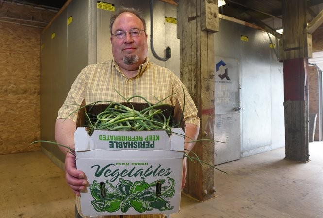 Neil Miller, founder and owner of Farmshed Harvest Food Hub holds a box of garlic scapes from Gillie Brook Farm at his former warehouse on Burnet Avenue.