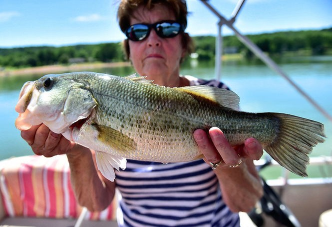 Sherry Whipple holds up a 17 1/2-inch largemouth bass she landed.