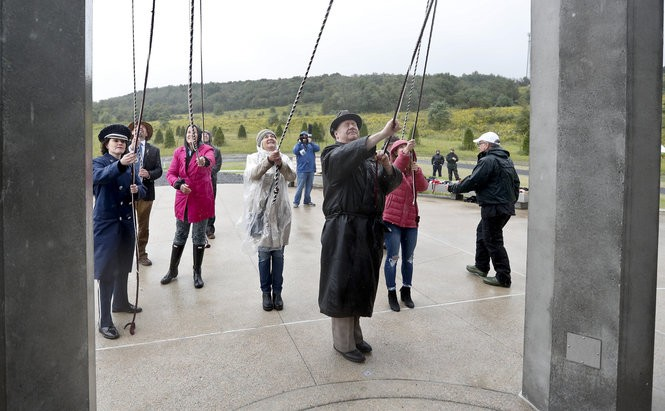 Members of passenger families, friends and volunteer representatives pull ropes to ring chimes at the dedication of the 93-foot tall Tower of Voices on Sunday at the Flight 93 National Memorial in Shanksville, Pa.