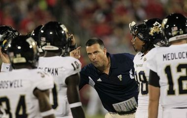 This Sept. 9, 2011 file photo shows Florida International coach Mario Cristobal talking with his players during the second half of their NCAA college football game against Louisville in Louisville, Ky. (AP photo)