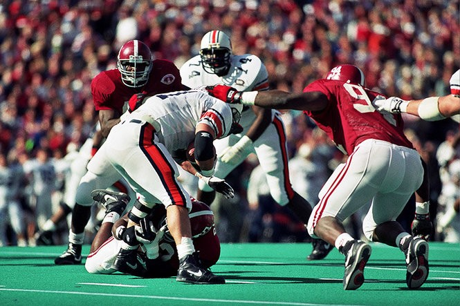 Alabama's John Copeland (94) takes down Auburn quarterback Stan White (11) during the 1992 Iron Bowl. (Photo courtesy of the Paul W. Bryant Museum)