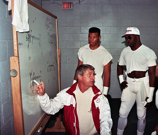 Alabama defensive backs coach Bill Oliver draws up a play for Eric Turner and Willie Gaston (in sunglasses).