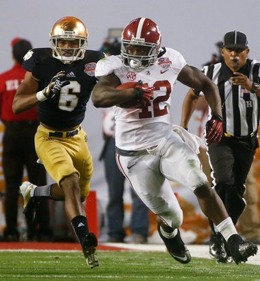 Offensive MVP Alabama's Eddie Lacy (42) runs past Notre Dame cornerback KeiVarae Russell during the second half of the BCS National Championship college football game Monday, Jan. 7, 2013, in Miami. (AP Photo/John Bazemore)