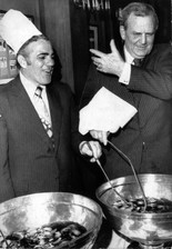 """University of Alabama football coach Paul """"Bear"""" Bryant reaches for, but misses, the chef's hat that's just fallen off his head as he stirs the pot at Antoines' Sugar Bowl banquet. Looking on is fellow-stirrer Ara Parseghian of Notre Dame, whose Fighting Irish met the Crimson Tide in the Sugar Bowl matchup."""