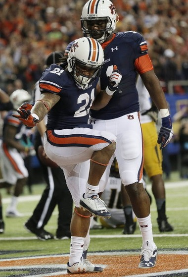 Auburn running back Tre Mason (21) strikes a Heisman pose as he celebrates a touchdown against Missouri during the second half of the Southeastern Conference Championship in Atlanta on Dec. 7, 2013. Mason was one of six finalists for the Heisman Trophy. (AP Photo/Dave Martin, File)