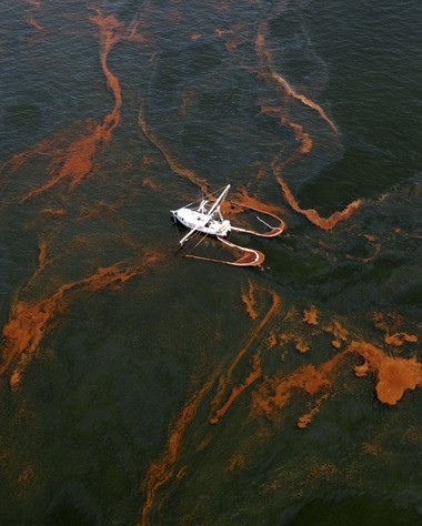 A shrimp boat skims off oil in May 2010 as the rusty ribbons drifted in the Gulf, pushed by the wind closer and closer to the shore line. (AP Photo/Eric Gay)