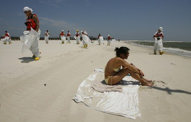 Sylvia Kellerman, on vacation from Germany and determined to enjoy the sun, basks on the public beach at Dauphin Island on May 12, 2010, as workers in protective suits look for tar balls. (Mike Kittrell, mkittrell@al.com)