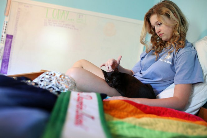 Carly Alexander, 15, Dauphin Island's 2015 Miss Dauphin Island, plays with her cats in her room in Dauphin Island, Ala., on April 23, 2016. (Sharon Steinmann/ssteinmann@al.com)