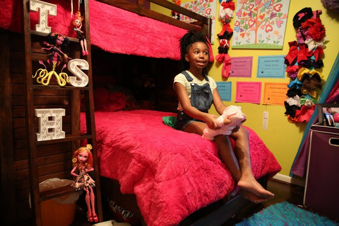 Tianna Harris, 10, plays with one of her many dolls in her room in Mobile, Ala., on March 13, 2016. Harris is the captain of the Adeeva Tigerettes dance team. (Sharon Steinmann/ssteinmann@al.com)