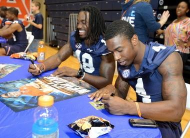 Auburn wide receivers Sammie Coates (18) and Quan Bray (4) sign autographs during Auburn Fan Day. (Julie Bennett/jbennett@al.com)