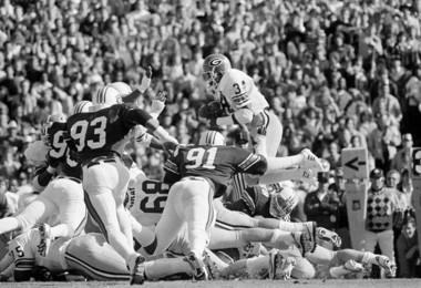 Georgia tailback Herschel Walker leaps for a first down on Saturday, Nov. 13,1982 at Auburn, Ala., despite Auburn defenders Quency Williams (93), Harold Hallman and Ben Thomas in first period. Georgia blockers are Jack Lindsay (59) and Warren Gray (68). (AP Photo/Joe Benton)