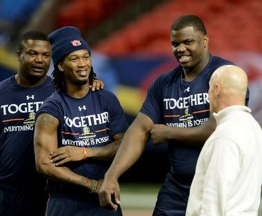 Auburn left tackle Greg Robinson, right, and wide receiver Trovon Reed, left, joke around with offensive line coach J.B. Grimes during Auburn's SEC Championship Game walk-through. (Julie Bennett/jbennett@al.com)