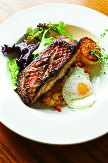"""The runny egg yolk melds the contrasting flavors and textures of the crispy pan-seared Gulf snapper and piquant creamed corn, Holland says. """"You take a bite of the fish. You take a bite of the corn. And then you pop the egg yolk, which ties it all together."""" (Photo by Melina Hammer)"""