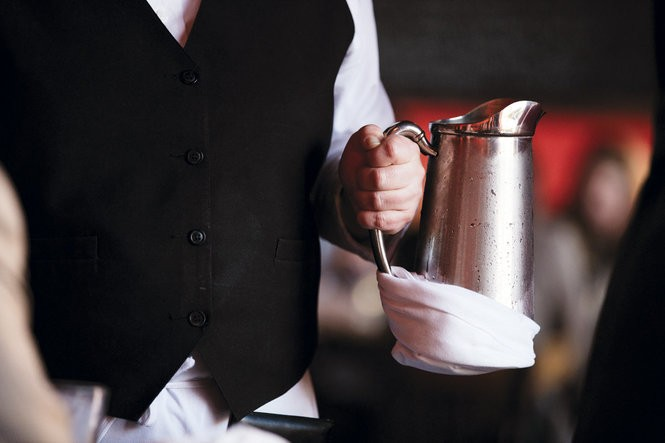 Waiters are taught the correct method for wrapping pitchers so they do not drip. Photo by Cary Norton.