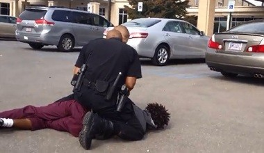A screenshot taken from a YouTube video involving Huntsville police officers arresting a man outside a church.