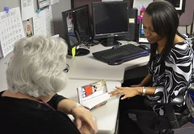 Jessica Etienne, a beneficiary services branch health care assistant who at an Army Medical Center Tricare Services Center, talks to a patient about her special medical needs and services that are available to her. (Contributed photo/Kim Zamarripa )