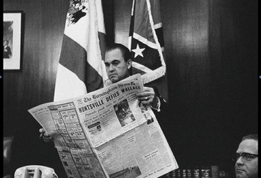 Gov. George Wallace reads about Huntsville's refusal to defy a federal court order to admit black students to its white schools in September, 1963. Huntsville defied Wallace instead and became the first city to integrate its schools in September of 1963 (file)