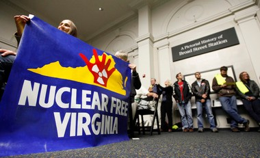 In this Tuesday Nov. 27, 2012, file photo, protesters hold a sign during a meeting of the Virginia Uranium Mining Working Group final informational public hearing at the Science Museum of Virginia in Richmond, Va.