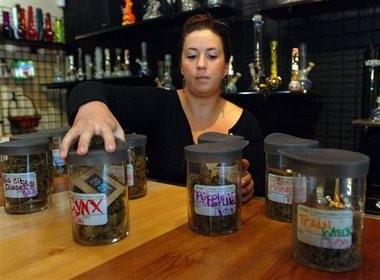 Danielle Baldwin arranges cannisters of medical marijuana at Puffs Smoke Shop in Ashland, Oregon. (Associated Press/Jeff Barnard)