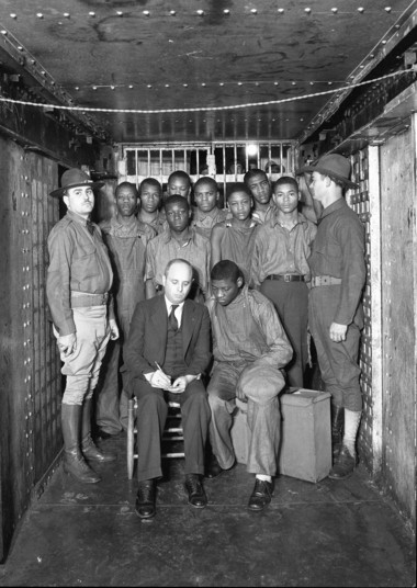 Two unidentified Alabama National Guardsmen are pictured with Scottsboro Boys in the Decatur City Jail. From left to right are Olen Montgomery, Clarence Norris, Willie Roberson, Roy Wright, Ozie Powell, Andy Wright, Charlie Weems and Eugene Williams. Seated in front Samuel Leibowitz, defense lawyer and Haywood Patterson, defendant. (Photo courtesy of Morgan County Archives)