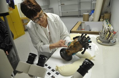 Birmingham Museum of Art conservator Margaret Burnham examines a sculpture depicting an African head of a woman, made of antelope skin and wood, to determine past repairs and possible new treatment.