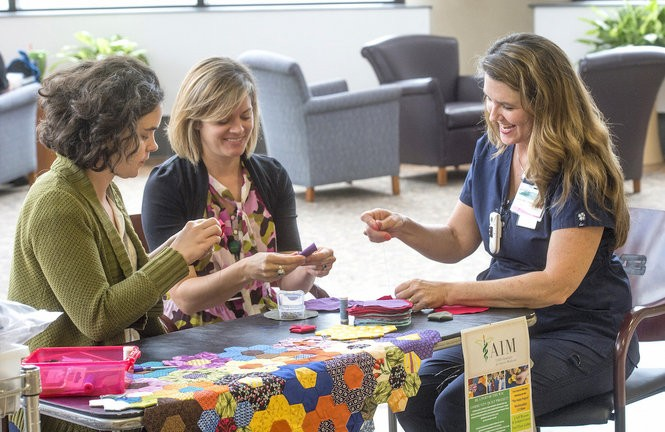"""From left, Lillis Taylor, Kimberly Kirklin and Sandra Holt Milstead work on """"hexies,"""" the building blocks for two quilts made from nursing scrubs at UAB's Women and Infants Center. (UAB photo/Steve Wood)"""